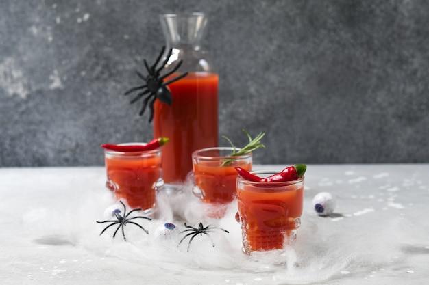 Coquetel de bloody mary ou suco de tomate em copos com formato de caveira