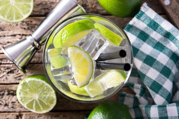 Coquetel de caipiroska com limão na mesa de madeira