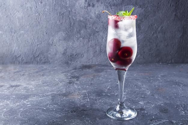 Coquetel de cereja fresca em taça de champanhe em plano de fundo texturizado cinza