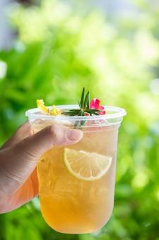 Coquetel de chá gelado de ervas com flores comestíveis em superfície de madeira