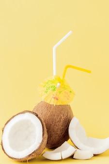 Coquetel de coco fresco com canudos em fundo amarelo