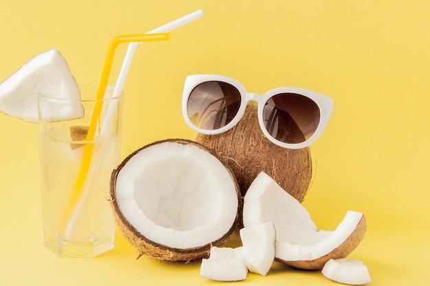 Coquetel de coco fresco com canudos em fundo amarelo.