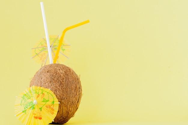 Coquetel de coco fresco com canudos no amarelo