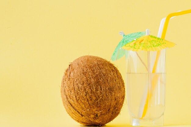 Coquetel de coco fresco com canudos no espaço de cópia de fundo amarelo