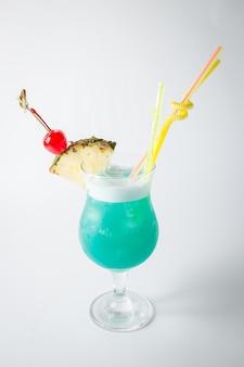Coquetel de curaçao azul fresco de álcool com abacaxi e bagas em fundo branco.