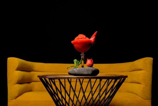 Coquetel de daiquiri de morango natural com fundo preto sobre uma mesa
