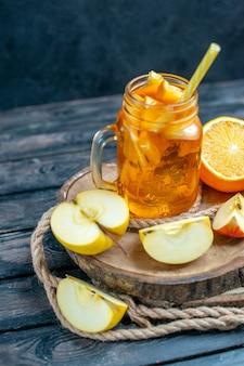 Coquetel de frente para cortar laranjas e maçãs em uma placa de madeira no escuro