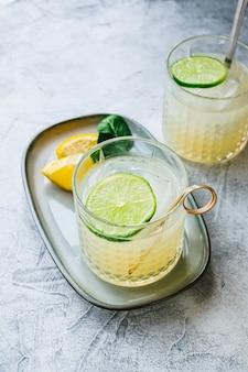 Coquetel de frutas cítricas com suco de limão e lima em um copo sobre a mesa