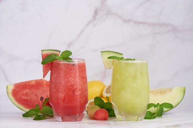 Coquetel de frutas cítricas refrescante com limão, melancia e melão com hortelã e cubos de gelo em copo