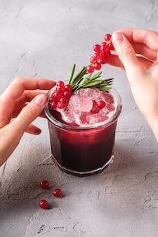 Coquetel de frutas frescas em copo, bebida refrescante de frutas vermelhas com folhas de alecrim no verão