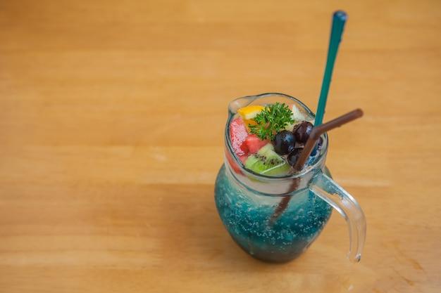 Coquetel de frutas gelado no pote de vidro no fundo madeira