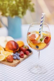 Coquetel de frutas na mesa de madeira branca com bagas e folhas de hortelã