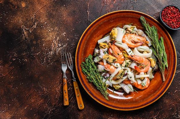 Coquetel de frutos do mar crus com camarões, camarões, mexilhões, lulas e polvos em uma tábua de cortar. copie o espaço