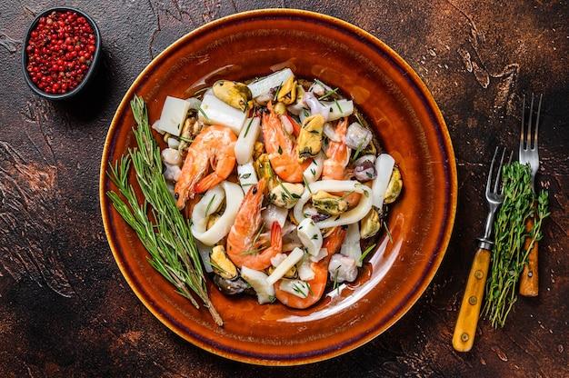 Coquetel de frutos do mar crus com camarões, camarões, mexilhões, lulas e polvos em uma tábua de cortar.