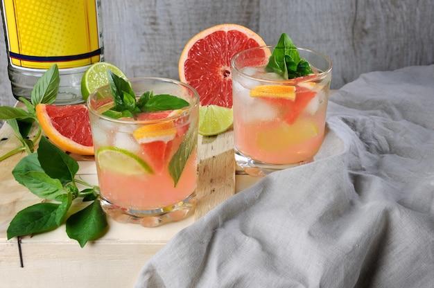 Coquetel de gin seco de londres com suco de toranja vermelha espremida e folhas de manjericão delicado com rodelas de limão e cubos de gelo resfriados