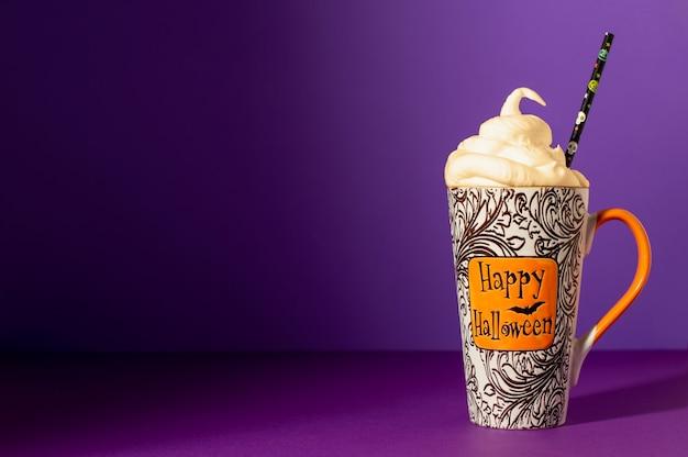 Coquetel de halloween feliz com espuma de chantilly e canudo na caneca alta sobre um fundo roxo.