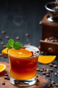 Coquetel de laranja e café na superfície escura.