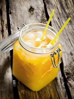 Coquetel de laranja fresca coquetel com gelo em uma jarra com canudo no fundo de madeira