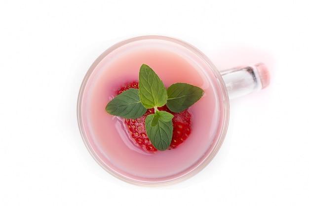 Coquetel de leite com morango com folhas de hortelã em um vidro transparente e frutas sobre um fundo claro.