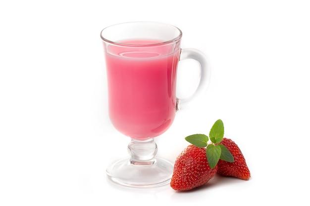 Coquetel de leite com morangos em um vidro transparente e folha de hortelã, fatias de morango em um fundo branco. Foto Premium