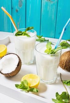Coquetel de leite vegan de coco em vidro com fundo de madeira.