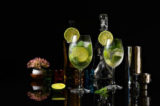 Coquetel de limão em uma taça de vidro sobre um fundo preto reflexivo gim e bebida tônica com limão
