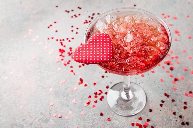 Coquetel de margarita vermelha fresca com corações sobre fundo cinza, conceitos de dia dos namorados