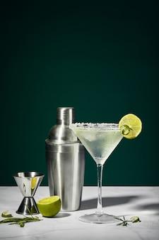 Coquetel de martini com gelo e uma fatia de limão e shaker sobre uma mesa de mármore um coquetel alcoólico ou não ...