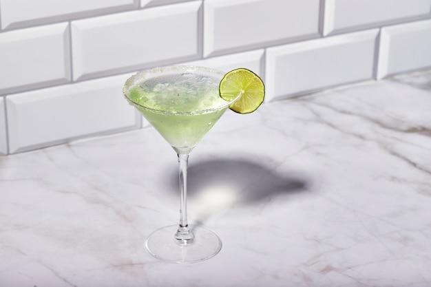 Coquetel de martini com gelo e uma fatia de limão no fundo da mesa de mármore coquetel alcoólico ou nonalco ...
