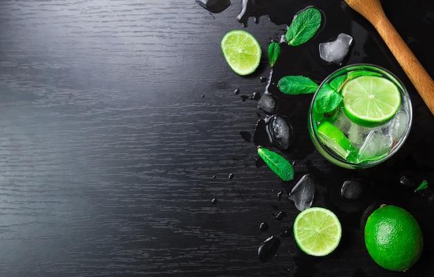 Coquetel de mojito com limão, folhas de hortelã e cubos de gelo em fundo preto. vista superior com espaço para texto.