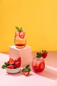 Coquetel de mojito de verão com morangos em fundo amarelo e pódio rosa. morango mojito. bebida refrescante de verão com espaço de cópia
