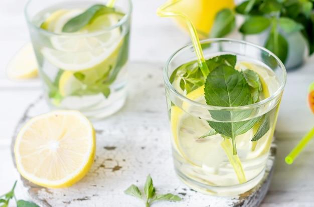 Coquetel de mojito em copo, limão e folhas de hortelã na cesta na mesa de madeira branca,