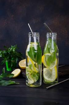 Coquetel de mojito em copo, limão e folhas de hortelã
