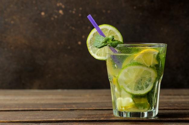 Coquetel de mojito em um copo com lima, hortelã e limão em uma mesa de madeira marrom