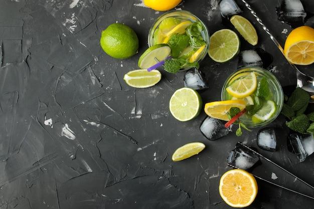 Coquetel de mojito em um copo com lima, menta e limão e acessórios de bar em fundo de concreto escuro. cozinhar mojito. vista do topo. lugar livre