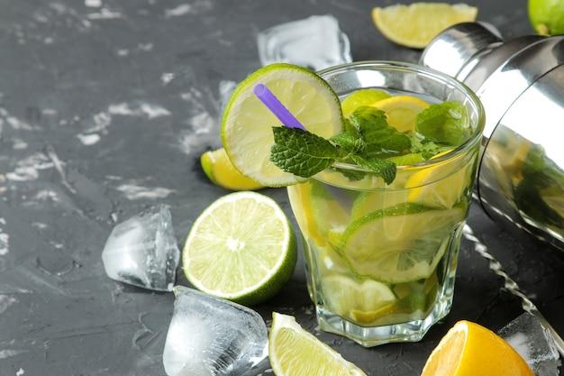 Coquetel de mojito em um copo com lima, menta e limão e acessórios de bar em fundo de concreto escuro. faça um mojito.