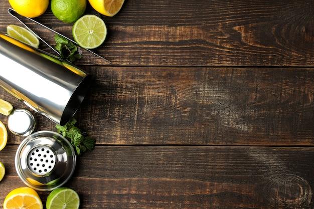 Coquetel de mojito em um copo com lima, menta e limão e acessórios de bar sobre uma mesa de madeira marrom. cozinhar mojito. vista do topo. lugar livre Foto Premium