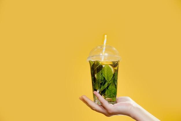 Coquetel de mojito em um copo de plástico com um tubo em um fundo amarelo. bebida fresca no verão para levar. lugar para texto.