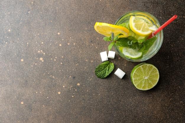 Coquetel de mojito em um copo de vidro com lima, menta e limão e sobre um fundo de concreto escuro. faça um mojito. vista do topo. lugar livre