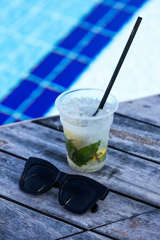 Coquetel de mojito em uma taça na beira da piscina ao ar livre