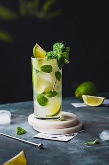 Coquetel de mojito frio com rum, limão, cubos de gelo e menta