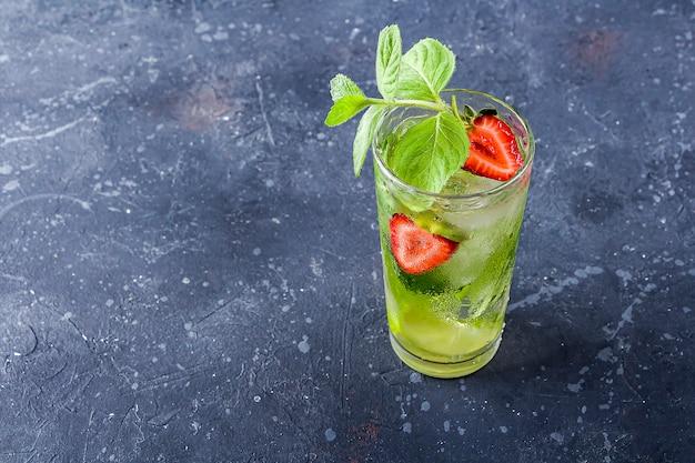 Coquetel de mojito limonada de verão ou chá gelado .bebida desintoxicante de refrigerante com morango, limão e hortelã