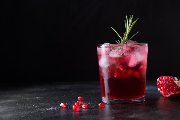 Coquetel de natal de romã com alecrim, champanhe, club soda na mesa preta. fechar-se.