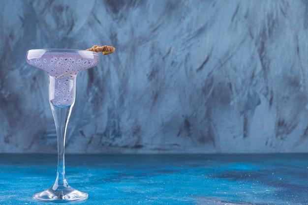 Coquetel de sementes de manjericão fresco colocado sobre fundo azul.