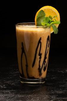 Coquetel de smoothie de frutas saudáveis com cobertura de banana, laranja e chocolate em um copo de vidro transparente.