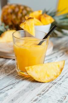 Coquetel de suco de abacaxi natural fresco ou suco de abacaxi fresco na mesa de madeira branca saboroso suco
