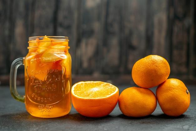 Coquetel de tangerinas frescas em vista frontal em um espaço escuro