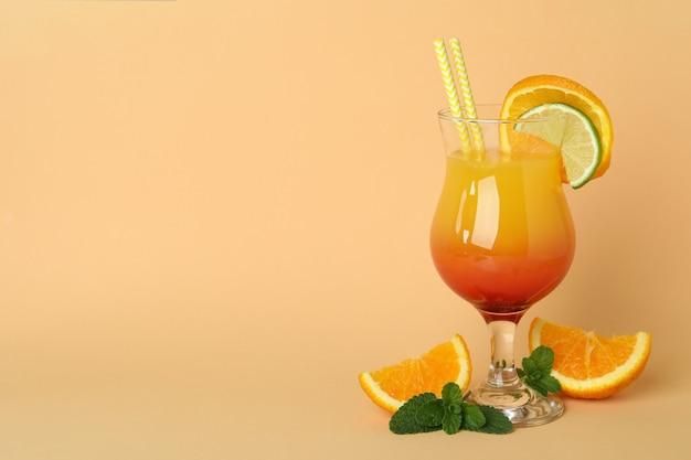 Coquetel de tequila ao nascer do sol e ingredientes em bege