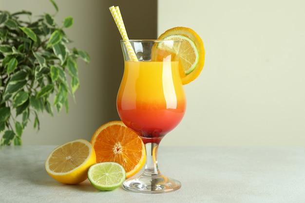 Coquetel de tequila ao nascer do sol e ingredientes na mesa texturizada branca