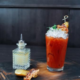 Coquetel de tomate com gelo decorado com rúcula e um pedaço de bacon. coquetel fica em uma mesa de madeira vintage em um bar ao lado de uma garrafa de cristal e uma fatia de pepino salgado e uma fatia de bacon.